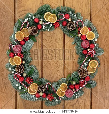 Christmas snow covered fir wreath decoration with dried orange fruit, candy canes, red and gold baubles, holly, mistletoe and pine cones on oak front door background.