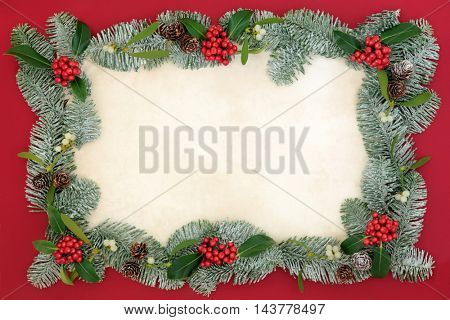 Christmas border with holly, mistletoe and snow covered spruce fir on old parchment paper over red background.