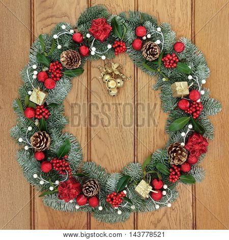 Christmas spruce fir wreath decoration with red and gold bauble and gift box decorations with dangling bells, holly, mistletoe and pine cones on oak front door background.