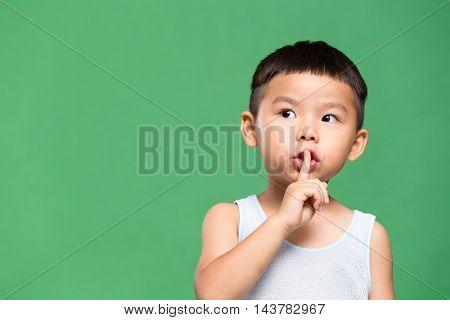 Little boy making a hush pose