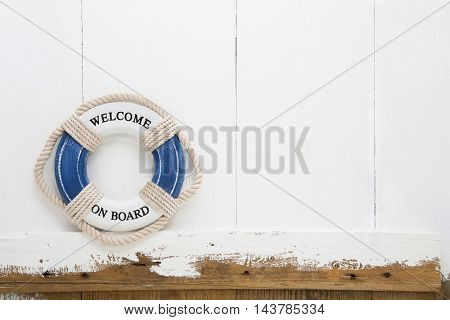 Welcome on board lifebuoy on white and blue old wooden background for concepts.