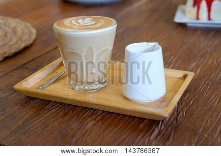 Hot Piccolo latte coffee serve with syrup on wooden tray in coffee shop.