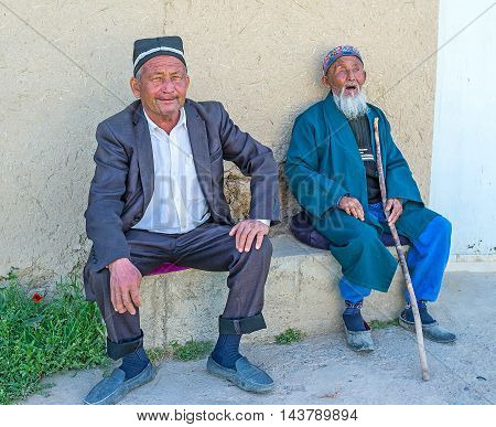 SAMAK UZBEKISTAN - MAY 2 2015: The senior man with the walking stick together with his elderly son in traditional skullcaps next to their house in kishlak (village) on May 2 in Samak.