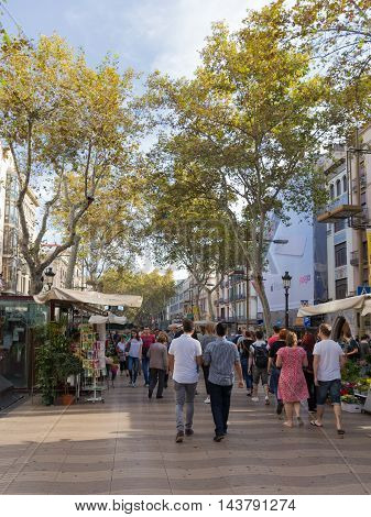 Barcelona - 10 October 2015: a crowd of people and happy tourists strolling on the main tourist street of beautiful Barcelona in Catalonia - Rambla October 10 2015 Barcelona Spain
