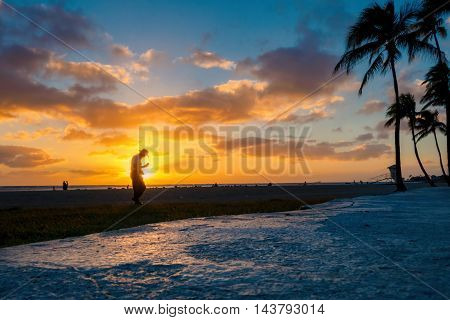 Honolulu, Hawaii, USA - Dec 21, 2015: Setting sun over beach at Ala Moana Park, along Ala Moana Park Drive. The beach overlooks Mamala Bay. A person walks in front of the setting sun.