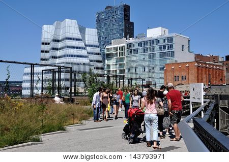 New York City - August 27 2010: View looking north along the High Line Park built atop a 1930's freight rail line on Manhattan's West Side with Frank Gehry's 2007 IAG Building on the left