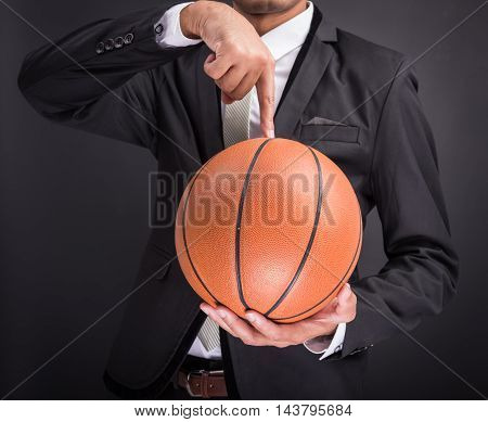 Young businessman holding basketball ball isolated on black background