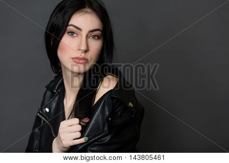 Portrait of beautiful brunnette model woman posing in studio. Serious lady in leather jacket posing isolated on black background.