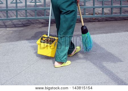 the janitor swept the city sidewalk from the fallen leaves
