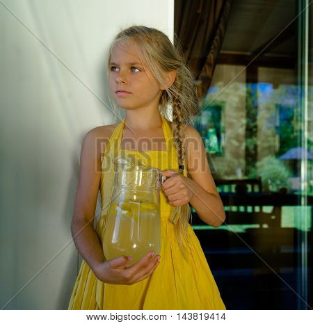 cute girl preparing lemonade in a glass jar
