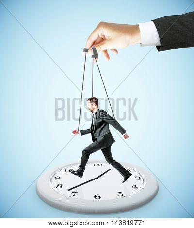 Huge hand making businessman run on abstract clock. Light blue background. Manipulation and control concept