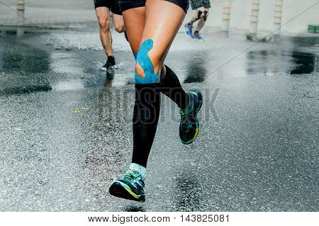 feet girl runners in compression socks and taping on his knees running on wet asphalt