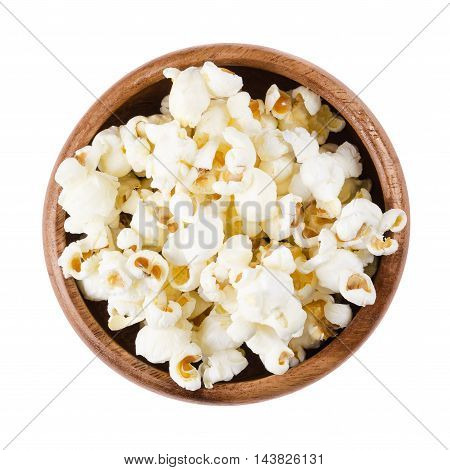 Popped popcorn in a wooden bowl on white background. Butterfly shaped popcorn puffed up from the kernels, after it has been heated. Edible, raw and vegan food. Isolated macro photo close up from above