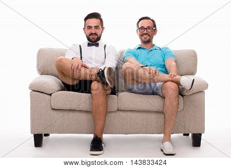 Two excited men sitting on couch or sofa and looking at camera isolated on white background. Happy men smiling and watching TV. Epressing emotions concept.