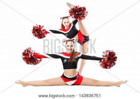 Two professional cheerleaders posing at studio. Side split and vertical split. Isolated over white.