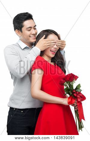 Asian man makes present to his lovely sweetheart. Young man giving a gift. Cheerful young couple man and woman at home offering to each other gifts for lover's valentine day