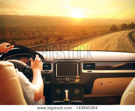 Male hands on car steering wheel. View from car windshield to road and beautiful landscape.