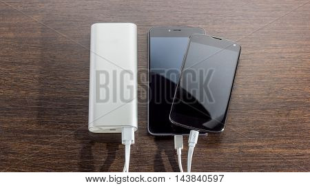 Power Bank charging two smartphones - dark wooden background, black phone, white power bank