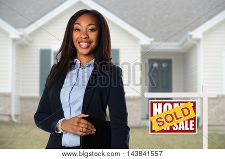 Beautiful African American Real Estate agent inf front of sold house