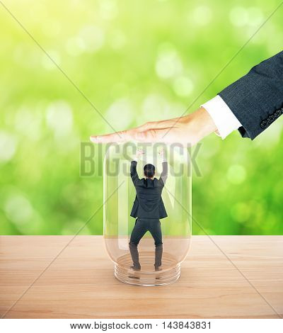 Employee miniature trapped inside transparent glass jar by employer's hand. Abstract green background
