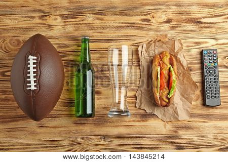 TV remote control, beer and ball on wooden background