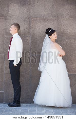 Unhappy newlyweds argue, having relationship difficulties. Marital problems concept. Couple after an argument ignoring each other. Side view portrait