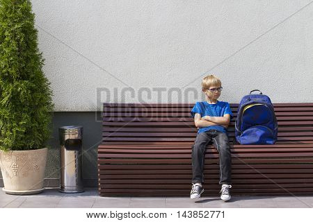 Boy with glasses sitting on the bench and waiting. Outdoors