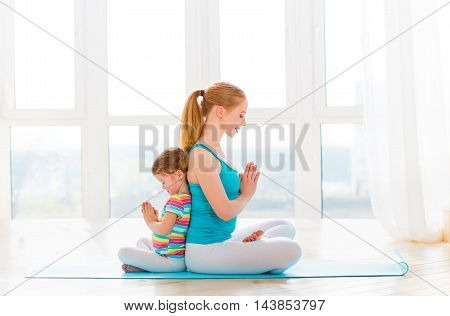 family mother and child daughter are engaged in meditation and yoga exercise at home