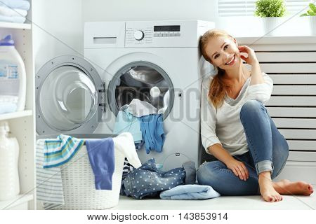 happy woman housewife in the laundry room near the washing machine with dirty clothes poster