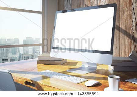 Side view of creative designer desktop with blank white computer screen keyboard coffee cup book and other items. Wooden wall and window with city view in the background. Mock up 3D Rendering