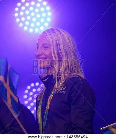 STOCKHOLM SWEDEN - AUG 21 2016: Happy swedish female wrestler Sofia Mattson waiving a flag when swedish olympic athletes are celebrated in Kungstradgarden StockholmSwedenAugust 212016