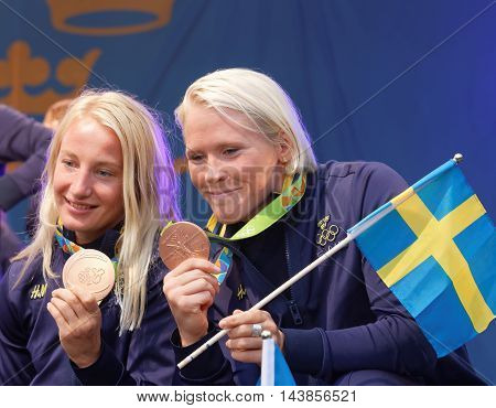 STOCKHOLM SWEDEN - AUG 21 2016: Happy swedish female wrestler Sofia Mattson and Jenny Fransson showing their medals when swedish olympic athletes are celebrated in Kungstradgarden StockholmSwedenAugust 212016