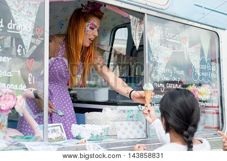 Lady With Red Hair Wearing Spotted Apron Serving Ice Cream