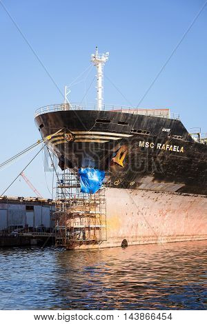 Naples Italy - August 10 2016: A ship docked in the port construction sites is repaired by damage to the bow. Scaffolds were placed to allow workers to work on the hull.