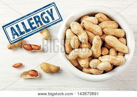 Allergy danger concept. Peanuts in bowl with stamp allergy on white wooden background.