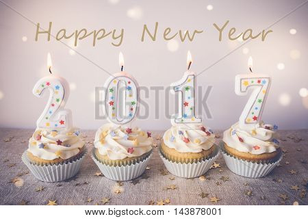 Happy New Year 2017 cupcakes with candles on fairy light toning background