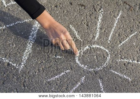 Hand girl draws by a chalk picture House and the Sun on asphalt in the great outdoors