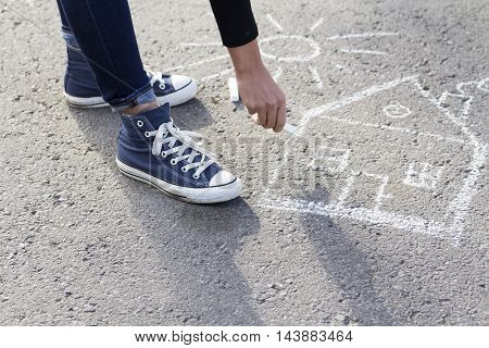 Girl draws by a chalk picture House and the Sun on asphalt