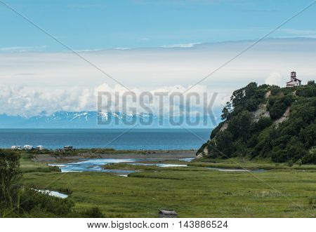 Scenic view of Deep Creek Alaska and Cook Inlet with volcano in distant background.