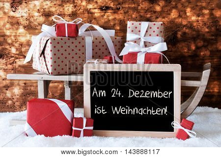 Chalkboard With German Text Am 24. Dezember Ist Weihnachten Means December 24th Is Christmas Eve. Sled With Christmas And Winter Decoration. Presents On Snow With Wooden Background And Bokeh Effect.