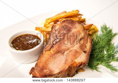Baked ham of pork neck stewed in wine with garlic Crans served with fried potatoes and mustard sauce