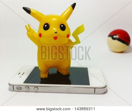 Nueva Esparta, Venezuela 21 august 2016. toy of caracter Pikachu from the anime pokemon above a iphone with a pokeball back representing the augmented reality game pokemon go,developed by Niantic for play in smart phones.
