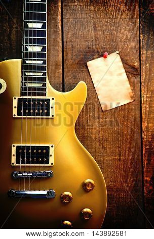 Gold single cutaway guitar on old wood surface and blank piece of paper, good for playlists, and production notes. Intentionally shot in surreal tone.