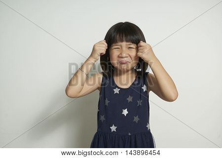 little girl rubbing her eyes crying .