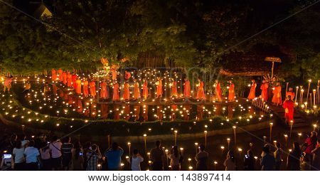 CHIANG MAI THAILAND - JULY 11: Unidentified Thai monks walking around buddha statue among many lanterns at Phan Tao temple in Asalha Puja Day on July 11 2014 in Chiang Mai Thailand.