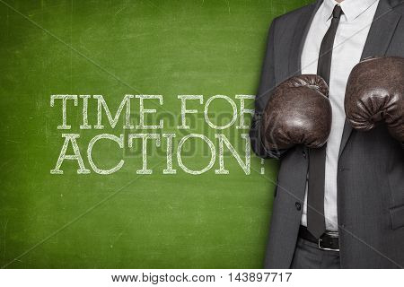 Time for action on blackboard with businessman wearing boxing gloves