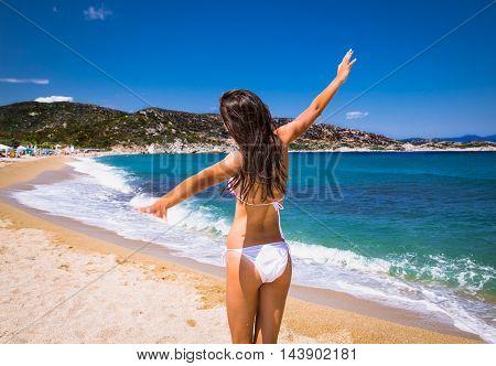Beautiful woman flying and enjoying on beach. Greece.