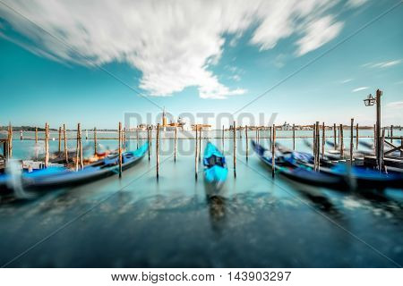 Venice landscape view on San Giorgio Maggiore island with gondolas on the foreground. Long exposure image technic with motion blurred gondolas and glossy water