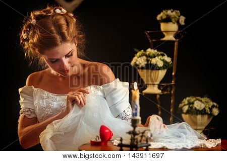 Happy girl in a wedding dress sits at table. On the table a box with a wedding ring and burning candle looking down on wedding dress.