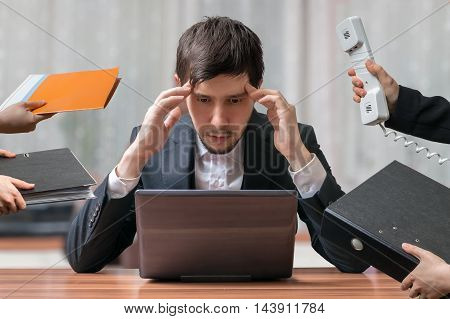 Young intend and thinking busy businessman is working with computer. Secretary and assistants around. Team work concept.